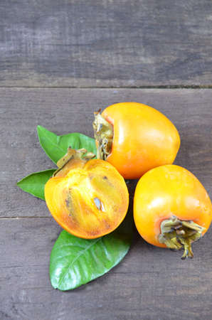 Delicious ripe persimmon fruit on wooden background Stock Photo