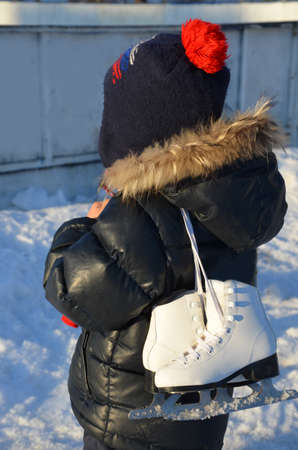 cute little boy wearing warm winter clothes going ice skating. skates for figure skating. skating rink on the street. enjoys winter. Winter sports