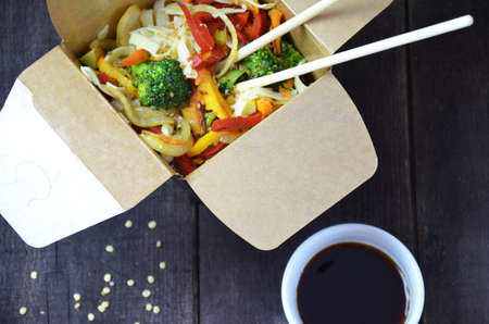 Chinese or korean food noodles on sticks. in the card box take out or to go. soy sauce. with vegetables on a wooden table