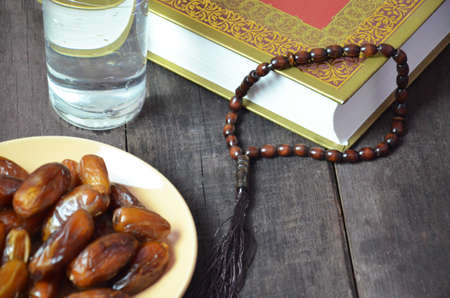 Silver bowl full of dry dates, glass of water for iftar and prayer rosary beads with holy Koran on black background. Ramadan month. Islamic religion concept.