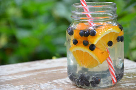 Infused detox water with blueberry, , orange. Ice cold summer cocktail or lemonade in glass mason jar against a background of green foliage. The concept of health, diet, weight loss, cleansing of toxins