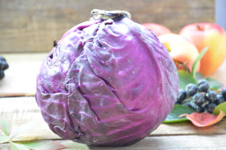 fresh purple red cabbage on cutting board on wood table with copy space. Homemade food concept. Autumn harvest. Background of fruit apples and grapes.