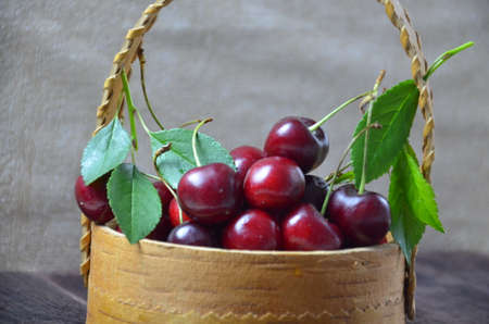 Fresh cherries in basket on wooden table Stock Photo