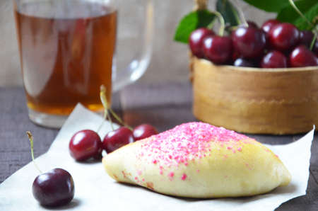 Cherry homemade russian pies on wooden background and cup of tea. with cherry in the basket Imagens