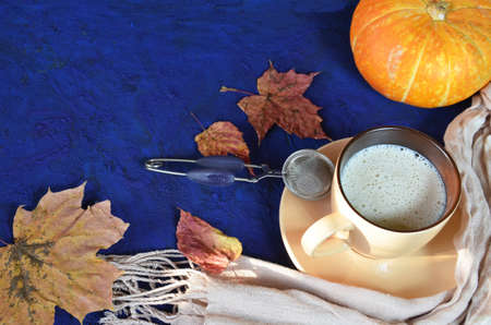Pumpkin spiced latte or coffee in cup, dry leaves, gifts on dark blue table. Autumn or winter hot drink. Space for text, top view, copy space