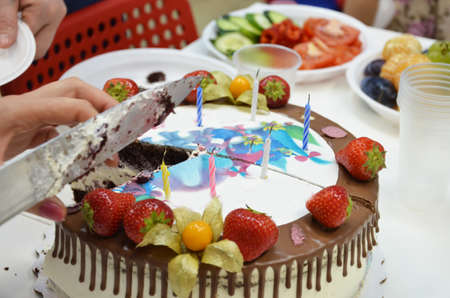 Hand cut the birthday cake with knifeBirthday cake with the inscription. A table full of sweets and snacks