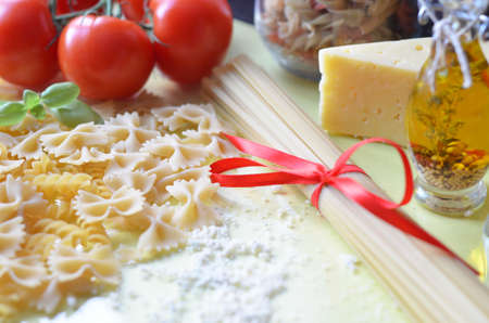 composition of healthy food ingredients on yellow white background, top view. Ingredients for making macron, spaghetti, pasta. Tomatoes, basil, parmesan cheese, grater