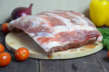 A piece of raw meat ribs for cooking with tomatoes and sweet peppers Balanced food background. Organic food for healthy nutrition. Meat beans and vegetables. Top view copy space at dark wooden table.
