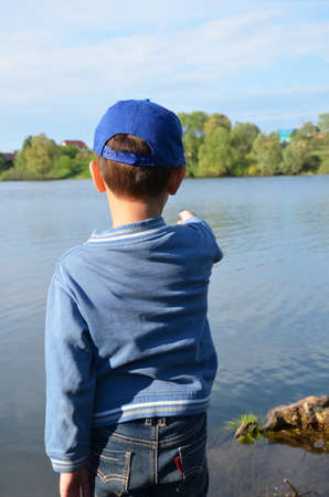 A boy stands by the forest lake and looks at the calm water. Nature, contemplation, inspiration, outdoor. Walk outdoors. loneliness. young cute boys fishing on a lake in a sunny summer or spring day.