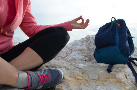 young woman meditation in a yoga pose at the beach. girl in lotus position on an empty stone seashore. takes yoga, sports, meditation. healthy lifestyle. close up sneakers sportswear. Stock fotó