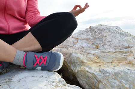 young woman meditation in a yoga pose at the beach. girl in lotus position on an empty stone seashore. takes yoga, sports, meditation. healthy lifestyle. close up sneakers sportswear. Reklamní fotografie - 118791402