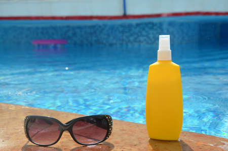 Sunscreen in a yellow jar with sunglasses on a background of blue pool water. The concept of rest, enjoying the sun, tanning, relaxation Foto de archivo