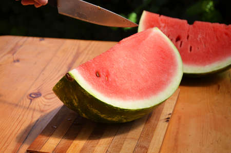 Three pieces of watermelon put on a chopping block. Chopper cutting a piece of water melon with knife. summer in Thailand. When everyone eats watermelons so delicious and fresh.