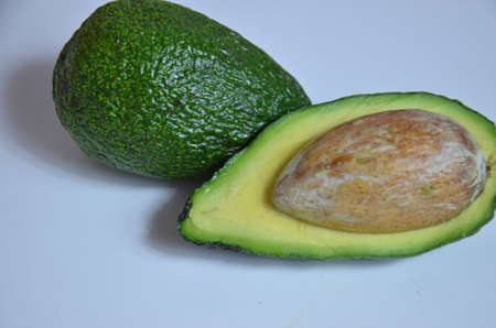 Natural organic ripe avocado. Half avocado on white background. Isolated. Top view.