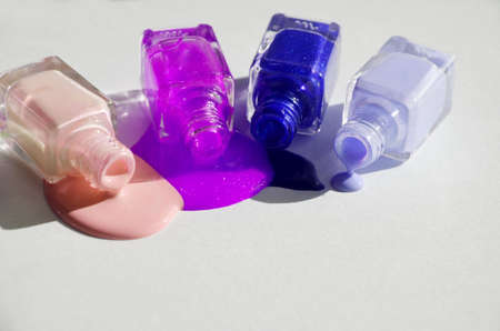 Bottles with spilled nail polish over white background.