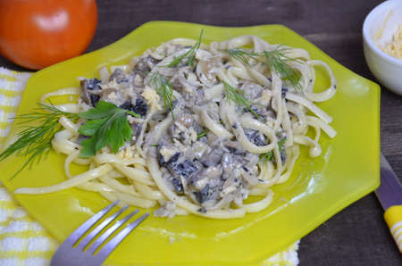 Pasta fettuccine with mushrooms and fried chicken ham in creamy cheese sauce on a dark wooden background.