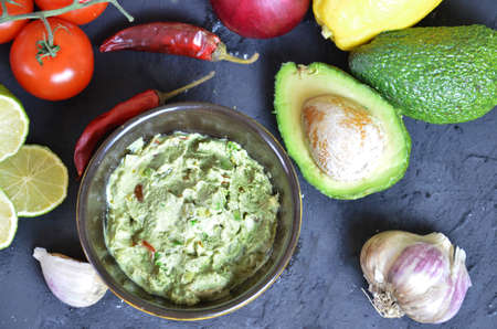 Bowl of freshly prepared guacamole. Ingredients on the background tomatoes, hot pepper, lime, avocado Guacamole nachos and guacamole ingredients on dark wooden background. 版權商用圖片