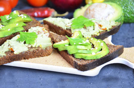 Guacamole with bread and avocado Sandwich with avocado and guacamole. Black cereal bread. Ingredients for making lime, red pepper, tomatoes. Healthy food, diet on a black background.