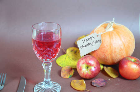 Thanksgiving Day. Pumpkin, pumpkin with autumn leaves and apples. Autumn harvest on a brown background. Happy Thanksgiving Lettering set table for celebration. fork and knife still life with bottle glass of red wine/