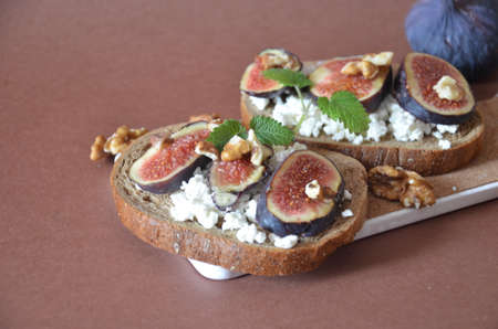 Sandwiches with ricotta, fresh figs, walnuts and honey. Canape or crostini with toasted baguette, cheese, jam, Delicious appetizer, ideal as an aperitif. Selective focus Stock Photo