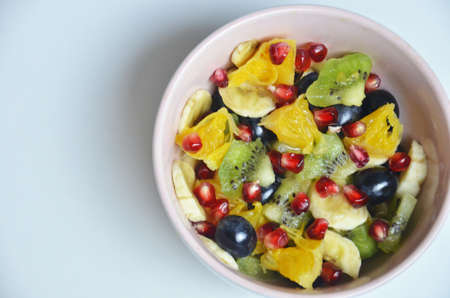 salad with fresh fruits and berries made from orange grapes and pomegranate and kiwi on a black background diet healthy nutrition vegetarianism.