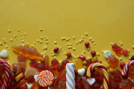 candies with jelly and sugar. colorful array of different childs sweets and treats on yellow background. red marmalade in the shape of a heart with a variety of caramels and candies, marshmallows. Abstract. top view copy space.