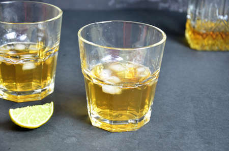 Drink cold tea with ice cubes and mint in two glass goblets a dark black background. Alcoholic or non-alcoholic mahito. whiskey or scotch tape, with lime or lemon