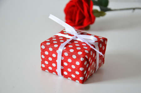 Homemade red present box with a gift tied with a ribbon, on a background a red rose on a white background, mothers day copy space of gifts for Christmas, valentines day, happy birthday, female hand.