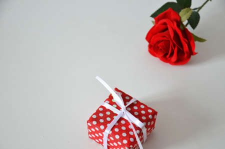 Homemade red present box with a gift tied with a ribbon, on a background a red rose on a white background, mothers day copy space of gifts for Christmas, valentines day, happy birthday, female hand Stock Photo
