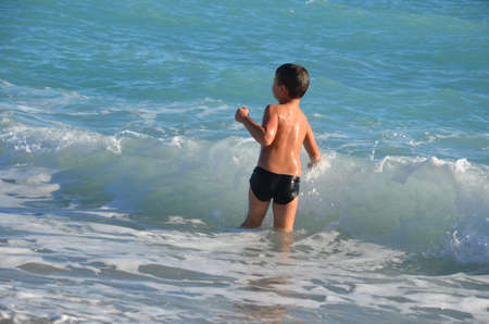 A small, happy boy stands in the water and splashes. A cheerful child jumps on the sea shore, the beach. The child enjoys the sea and splashes in the water with cottage cheese. Rear view