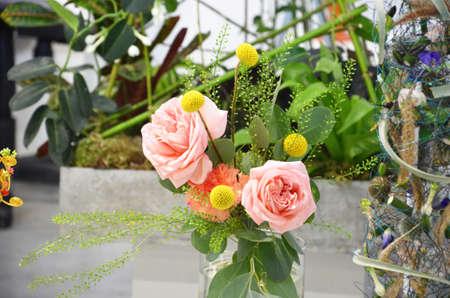 Blumenladenkonzept Florist kreiert Blumen in einem Weidenkorb. Schöner Strauß gemischter Blumen. frischer Haufen. Blumenlieferung. Bunter Strauß verschiedener Orchideen, Rosen, Freesien-Eukalyptusblätter Standard-Bild