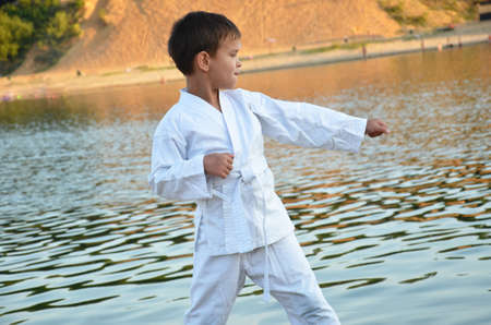 One little boy in white kimono during training karate kata exercises in summer outdoors. against the backdrop of a lake or sea during a beautiful sunset Stock fotó