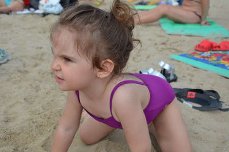 girl playing on the beach on summer holidays. Children building a sandcastle at sea