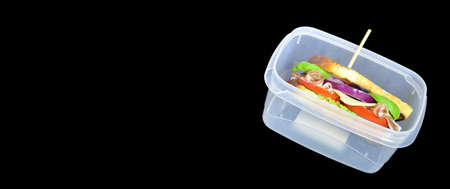 Healthy grilled Sandwich toast with lettuce, ham, cheese and tomato on a dark black background close up. Lunch box with sandwich concept back to school on school blackboard banner
