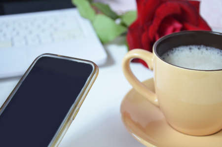 background of a cup with a coffee cappuccino mock up and a laptop on the desktop, red rose shot of young business woman working on his laptop and using smart phone sitting at wooden table in a coffee shop or office.