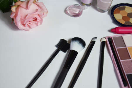 make-up brushes in holder and cosmetics isolated on white. lipstick, eye shadow, pink nail polish and pink rose