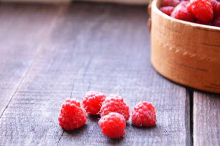 Fresh ripe raspberries in the wicker basket on wooden table
