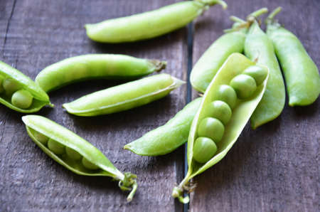 fresh green peas, just harvest. close up view of opened pod. spring vegetable up view on the wooden background Archivio Fotografico