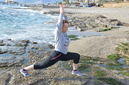 Beautiful blond girl clothing in at the seaside on the rock doing yoga poses, stretching or sports gymnastics and meditating in yoga pose.
