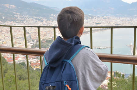 Little boy, looking at the amazing view on the Mediterranian sea gulf with touristic ships and aincient castle and a city from the mountain with a backpack on the back Archivio Fotografico