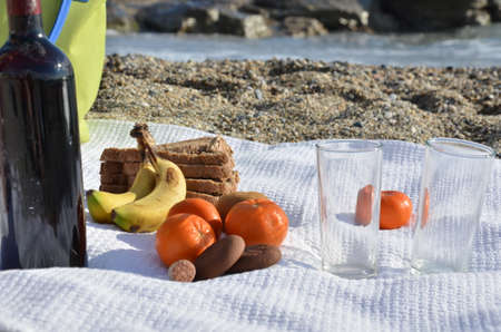 A party on the beach at sunset with wine. Romantic day evening in the summer by the sea. Picnic. copy space, Archivio Fotografico