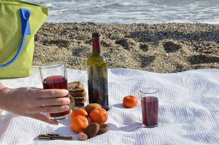 A party on the beach at sunset with wine. Romantic day evening in the summer by the sea. Picnic. copy space