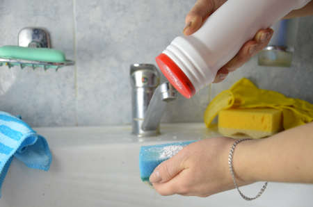 girl pours cleaning agent onto a sponge to wash the bathroom sink. Detail of woman hands washinga a sink in kitchen. Female hands doing housework over the sink
