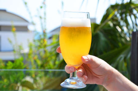 Hand holding a glass of beer in beach tropical sea background. vacation holiday concept Archivio Fotografico