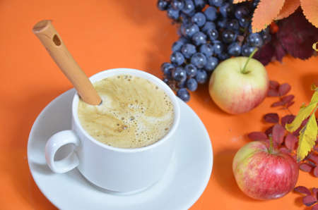 White cup of coffee with cappuccino cream on an orange background with autumn leaves, apples and red berries. Fall season, leisure time and coffee break concept. Banque d'images