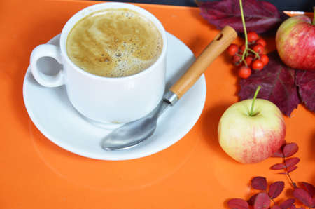 White cup of coffee with cappuccino cream on an orange background with autumn leaves, apples and red berries. Fall season, leisure time and coffee break concept. Autumn leaves and hot steaming coffee