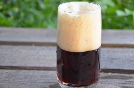 Glass of dark beer on the wooden background Archivio Fotografico