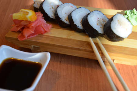 Salmon and caviar rolls served on a plate sushi rolls on a table in a restaurant on a wooden stand with chopsticks. with soy sauce, red ginger and orange