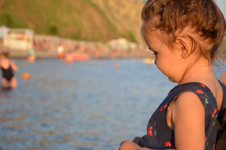 little girl with hair bundled at the seashore .