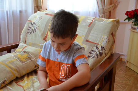boy reading book at home.